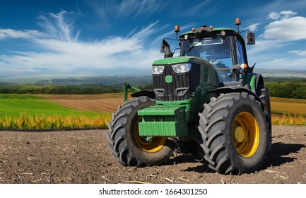 Russia, Krasnodar region, Kushevsky district.16.10.2018.   Modern, green tractor in the spring field work on the background of a beautiful rural landscape.
