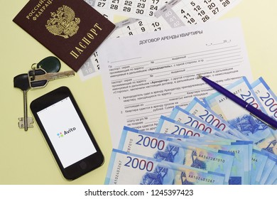 Russia, Krasnodar-November 11, 2018: Russian apartment lease Agreement, passport, keys and money. Search for accommodation using the AVITO mobile app