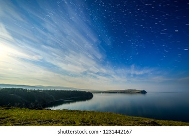Russia, Lake Baikal, Olkhon Island, Clouds and Stars on the Small Sea Bay. Cape Sagan-Khushun