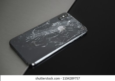 Russia, may 2018, Rostov-on-Don. Black smartphone Iphone X broken glass on the back cover of the phone close up.
