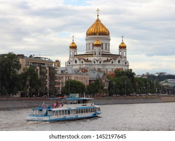 Russia / Moscow - 07 02 2019: Tourist ship Alina Prima floating on the Moscow river against the background of the Cathedral of Christ the Savior summer day, view of Moscow from the Crimean embankment