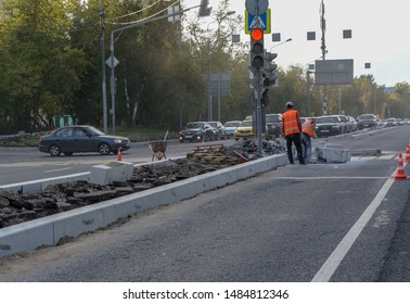 Russia. Moscow. 07.08.2019. Two workers are laying concrete curbs on a street in Moscow. Updating the pavement. Repair of road infrastructure.