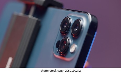 Russia - Moscow, 09.28.2021: extreme close up of cameras of a new Iphone 13 pro max fixed by steadicam. Action. New smartphone isolated on purple wall background.