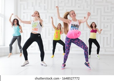 RUSSIA, MOSCOW, 2017 - MARCH 12: Group of young happy women wearing colorful sportswear dancing at Zumba class