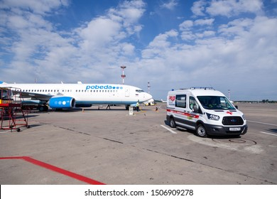 Russia Moscow 2019-06-17 Ford ambulance car on the background of the airport runway, large wide body passenger aircraft  Boeing 737 plane of Pobeda Airlines