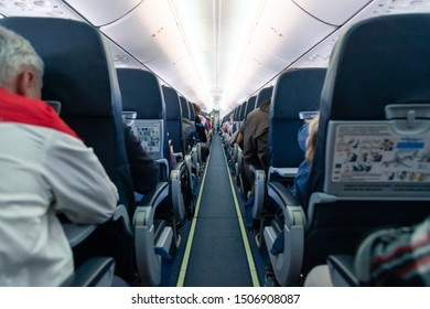 Russia Moscow 2019-06-17 Interior of large passengers airplane with passengers people on seats and stewardess in uniform walking the aisle, waiting to take off, for the plane taking off from runway