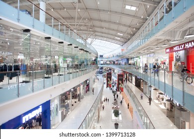 Russia, Moscow - April 12, 2019: Modern Interior of clothing store in big shopping center Aviapark. Atrium. Led lighting. Ceiling lights in the mall. Customers in store.