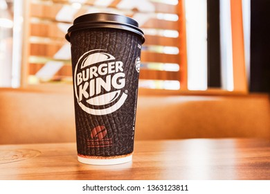 Russia, Moscow - April 2019: Close-Up Burger King Hot Coffee Cup On Wooden Table With Blur Burger King Interior For Background.
