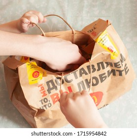 Russia, Moscow, April 2020: on the table is a packing paper bag for McDonald's, children's hands open the bag for homemade food. Delivery concept Illustrative version of the goods.