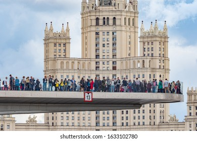 Russia. Moscow. A crowd of people on a hovering bridge over the Moscow river. Hovering bridge with transparent railings. The Zaryadye Park. Hovering bridge and a high-rise building. 19.07.2019