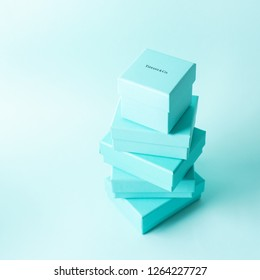 Russia, Moscow - December 21, 2018: Close view the stack of Tiffany boxes tied with silk ribbon, lying on each other on tiffany blue color pastel background. Gift festive selection.