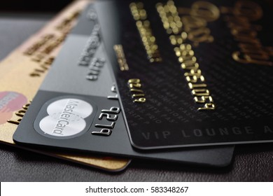 RUSSIA, MOSCOW - FEB 22, 2015: Premium credit cards MasterCard Black Edition, Gold Edition and Priority Pass access card on the black leather background. Small depth of field