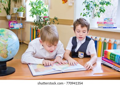 Russia, Moscow, first high school, 2 class b - October 28, 2017: Two small schoolboys, sitting together at table in class, reading the study book.