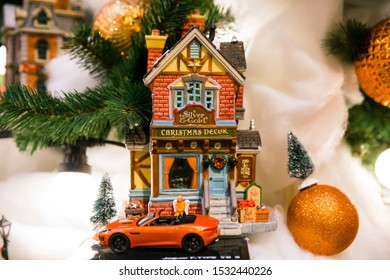Russia, Moscow, Gum deli, 20.12 2018. Installation, scene - toy brick house Christmas decor  with toy brown car orange and Christmas tree among Christmas light bulbs and orange balls close-up. Winter