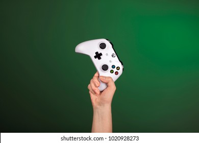 RUSSIA, MOSCOW, JANUARY 2017 Hand is holding xbox one s gamepad against a green background