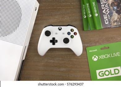 RUSSIA, MOSCOW, JANUARY 2017  View from the top on xbox one s gamepad, xbox one s game console, game discs and xbox live gold card laying on the table, January 2017.