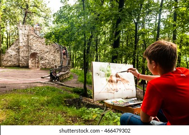 RUSSIA, MOSCOW - JULY 18, 2016: Museum-reserve Tsaritsyno. The old Palace ensemble of the XVIII century.  boy draws paints the picture of the tower ruins.