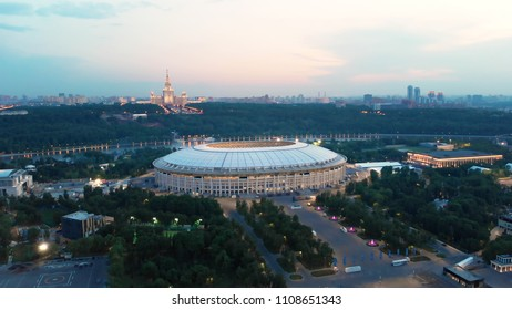 RUSSIA MOSCOW JUNE 2018: Flying above FIFA 2018 stadium Luzhniki in the late evening. Lights of night Moscow and one of the most important city highways. Moscow-city towers on the horizon.