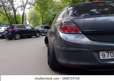 Russia, Moscow - May 04, 2019: Gray metallic Opel Astra modified to Stance style. Car with big custom steel wheels parked on the street. Back and right side view