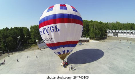 RUSSIA, MOSCOW - MAY 18, 2014: People stand near basket of air balloon with inscription Saint Russia in park Sokolniki at spring sunny day. Aerial view