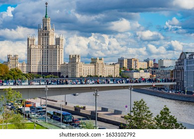 Russia. Moscow. People walk and sit on the Hovering bridge in Moscow. Modern Hovering bridge on the background of a high-rise building on Kotelnicheskaya embankment. 19.07.2019