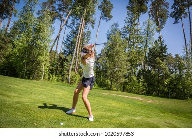 Russia Moscow region Nakhabino 05.31.2016 Young sportive beautiful european women playing golf on a golf course with gorgeous green. Forest, blue sky as background. Active senior lifestyle. Sunny day
