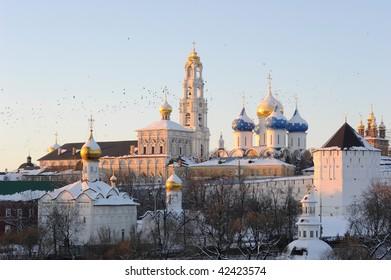 Russia. Moscow region. Sergiev Posad. Ensemble of Troitse-Sergieva Lavra at a sunset and birds flighting. Winter postcard