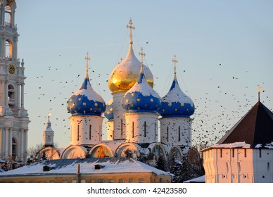 Russia. Moscow region. Sergiev Posad. Troitse-Sergieva Lavra at a sunset. Whirl of a flock of birds between domes. Winter postcard