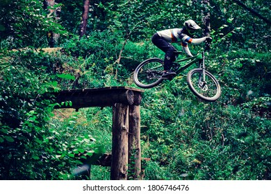 Russia, Moscow - Sep 01, 2020: Young boy jumping with his MTB Bike at forest. Professional downhill riding. Biker riding in nature. Cool athlete cyclist on a bike. MTB biking.