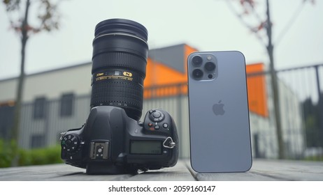 RUSSIA, MOSCOW - SEPTEMBER 27, 2021: Camera and phone comparison. Action. Professional camera with lens or new iPhone. Comparison of cameras of new iPhone 13 pro with professional camera