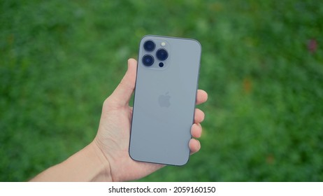 RUSSIA, MOSCOW - SEPTEMBER 27, 2021: New phone with professional cameras in hand. Action. Man is holding new iPhone 13 pro in hand. New iPhone with stylish design and improved camera