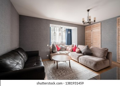 Russia, Nizhny Novgorod - April 26, 2019: Private apartment. Modern living room with Leather sofa, armchair, wooden coffee table and Tv. pillows on cozy sofa and lamps. Interior design