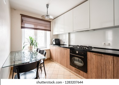 Russia, Nizhny Novgorod - January 10, 2018: Private apartment. Interior design. Small modern kitchen in white and wenge colors. dining table, gas cooker, coffee machine.