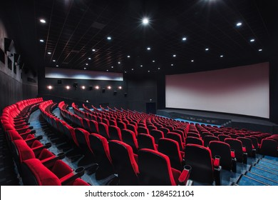 Russia, Nizhny Novgorod - may 29, 2014: October Cinema. Empty red cinema hall seats, comfortable and soft chairs. Perspective auditorium view.
