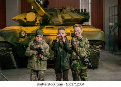 Russia, Nizhny Tagil, April 12, 2018: small children in khaki clothes on a tank with a toy weapon, the concept of children and war, the value of children's life. Postcard by may 9.