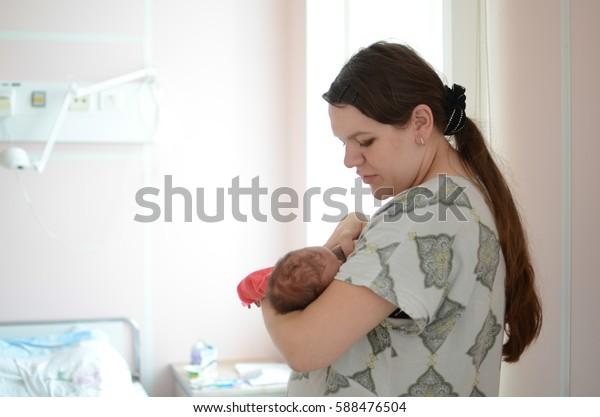 Russia, Nizhny Tagil: July 29 , 2013. Maternity hospital, mom and newborn twins.