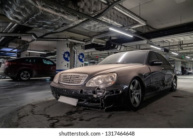 Russia, Novosibirsk, 2019-02-11. Black dusty abandoned Mercedes Benz sedan with broken air suspension stands in underground parking lot of shopping center. Concept of hacking and carjacking