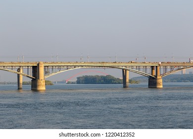 Russia, Novosibirsk, The Red Arch of the Bugrinsky Bridge is visible in the arch of the Communal Bridge