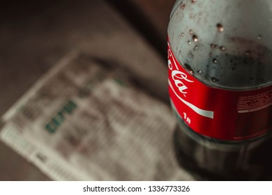 Russia, Orenburg - July 2016. A large plastic bottle of Coca Cola is on the old newspaper.