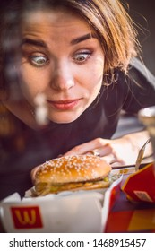 Russia; Orenburg - June 6 2019. McDonald's restaurant on Chkalova street; young beautiful girl with delight looks at a hamburger in a restaurant; portrait vertical photography