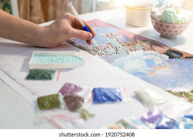 russia, rossosh - 02.05.2021: home hobby-to draw pictures of rhinestones, multi-colored diamond mosaic. the process of gluing pencil rhinestones on canvas pictures of the house on the table