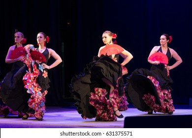 RUSSIA, RYAZAN - DECEMBER 11, 2016: V RUSSIAN FESTIVAL FLAMENCO. A SHOW OF A FEMALE TEAM IN FLORAL DRESSES WITH FANS AND RED FLOWERS IN THEIR HAIR.