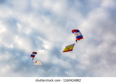 Russia Ryazan region Shilovo. 07.26.2018 Two colorful parachutes with colorful flages on the dramatic sky with clouds. Parachute jumps. Active life style.