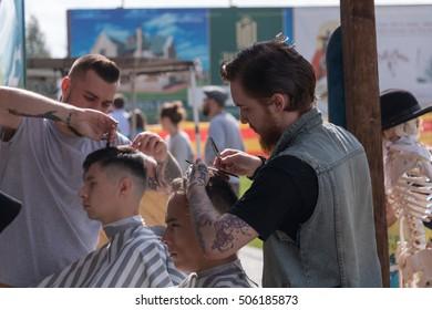 Russia. Saint - Petersburg. August 2016. Barbershop on the street. A man cuts hair. Tattoo, Smoking,