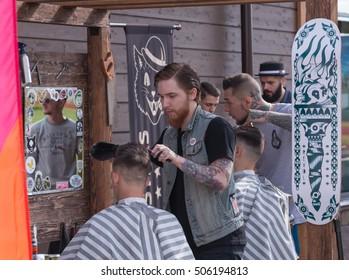 Russia. Saint - Petersburg. August 2016. Barbershop on the street. A man cuts a man. Tattoo, Smoking,