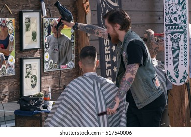 Russia. Saint - Petersburg. August 2016. Barbershop on the street. A man cuts a man. Tattoo, Smoking,