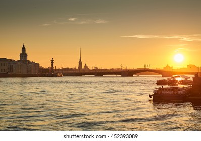 Russia, Saint-Petersburg, 03 July 2016: Closing of Palace Bridge at sunrise, the Peter and Paul Fortress, Spire in the orange sky, Rostral colomn, ships, boats, the traffic beginning, sun,