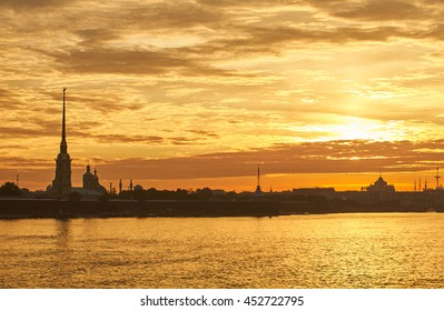 Russia, Saint-Petersburg, 29 June 2016:  The Peter and Paul Fortress at sunrise, Spire with angel in the orange sky, reflections, dramatic sky