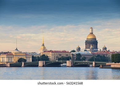 Russia, Saint-Petersburg, 29 June 2016:  The Vasilievskiy Island at sunrise, Rostral Columns, Isaacs Cathedral, Golden Dome,  Admiralty, Palace Bridge, water reflections