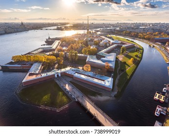 Russia, Saint-Petersburg,  Aerial view of Peter and Paul cathedral at sunset, walls of fortress, Golden autumn, panorama landscape, sunny day, golden spire with cross and angel, drawbridges, hermitage